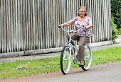 Smiling senior woman posing outside riding a bicycle