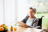 Senior woman in a wheelchair with tablet at home. An elderly woman sitting at the table.