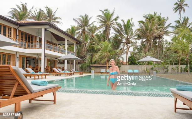 Senior woman in bikini standing in swimming pool