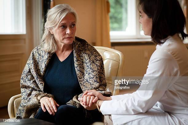 Femme âgée au soin maison est l'attention de femme médecin