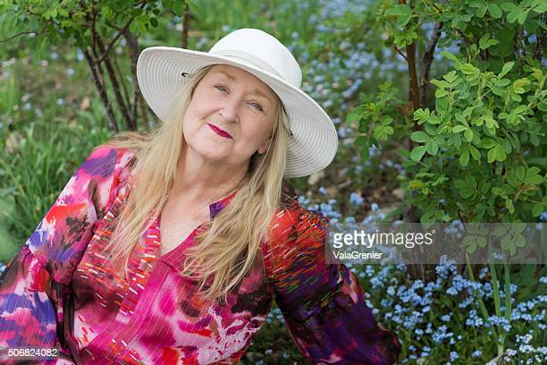 Senior mujer en blusa de colores relaja en la primavera de jardín.