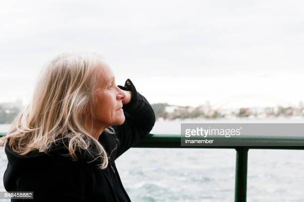 Senior woman in deep thought looking over bay, copy space