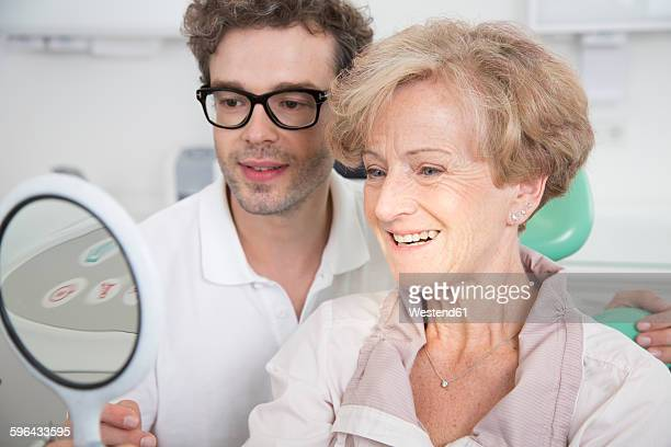Senior woman in dentists chair checking her teeth in mirror
