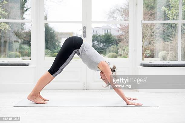 Senior woman in downward dog position