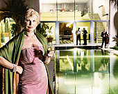 Senior Woman in Evening Wear Holding a Glass of Champagne Stands at the Poolside of Her Mansion Home, Her Dinner Party Guests in the Background