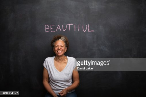 Senior woman in front of blackboard and the word beautiful : Stock Photo