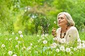 Portrait of a beautiful senior woman in green field with dandelions