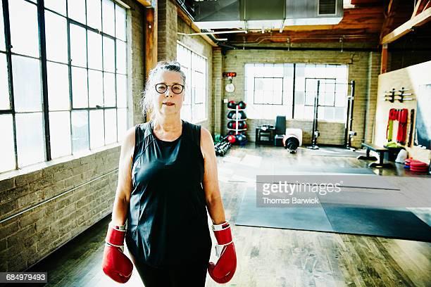 Senior woman in gym wearing boxing gloves