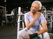 Senior woman in gym wearing wrist strap, rubbing shoulder