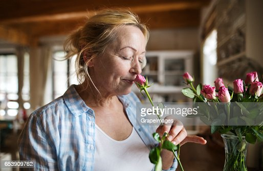 Senior woman in her kitchen smelling fragrance of pink rose : Stock Photo