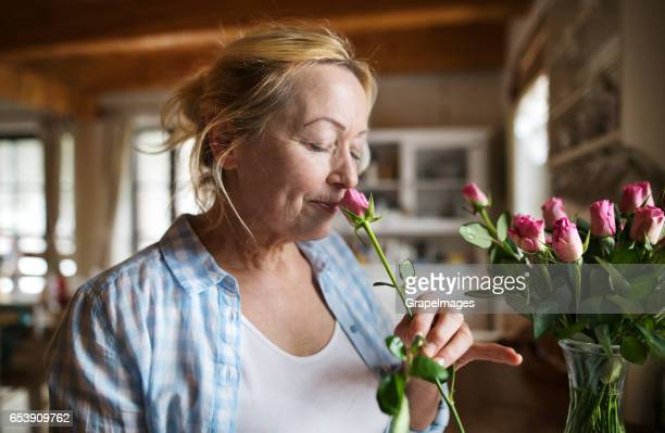 Senior woman in her kitchen smelling fragrance of pink rose