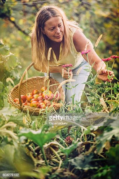 Senior Woman in her Vegetable Garden Smelling Flowers