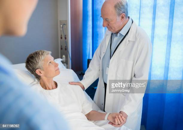 Senior woman in hospital bed, doctor holding her hand