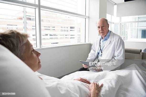 Senior woman in hospital bed talking to doctor