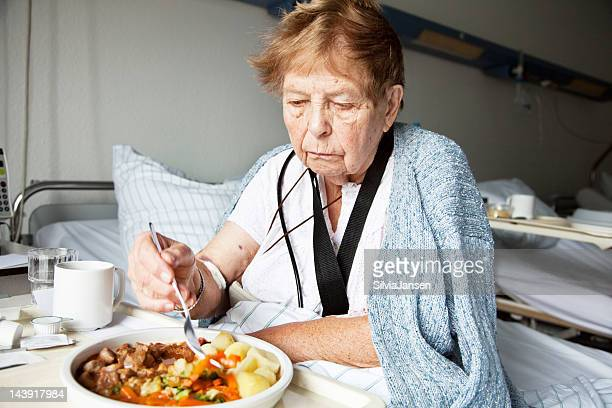 senior woman in hospital eating
