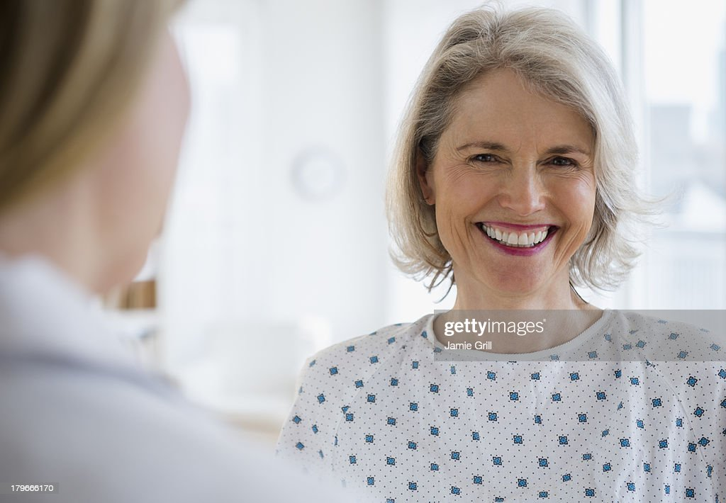 Senior woman in hospital gown, smiling