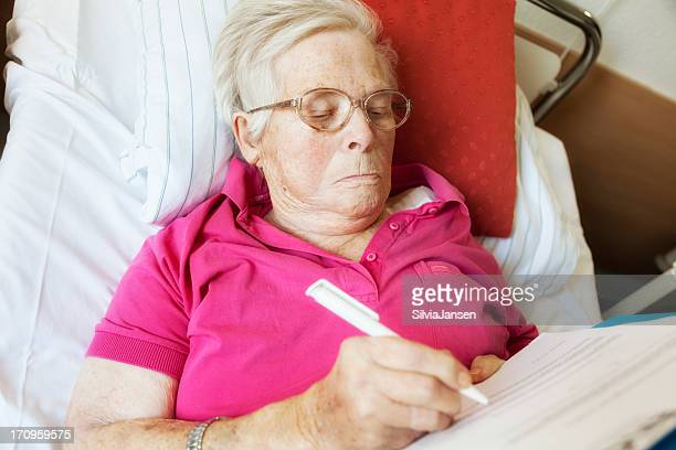 senior woman in hospital signing paper last will