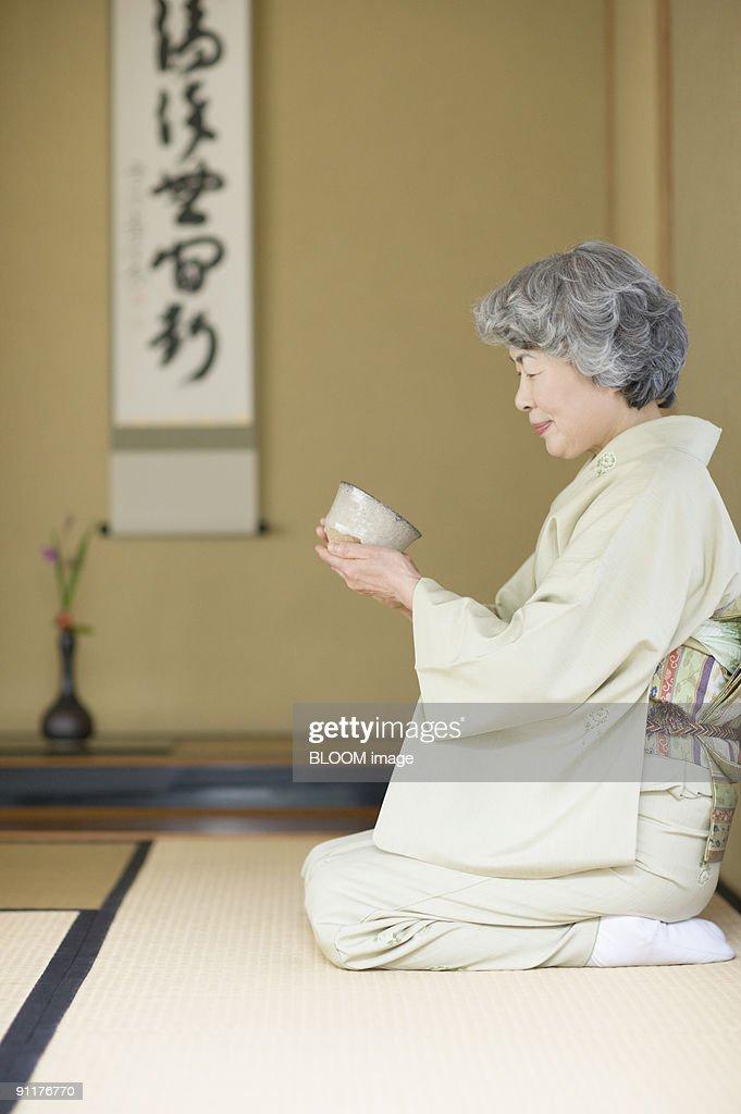 Senior woman in kimono holding Japanese tea cup : Stock Photo