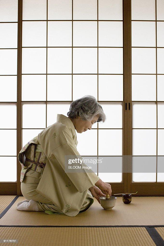 Senior woman in kimono preparing Japanese tea : Stock Photo