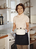 Senior woman in kitchen holding casserole dish, smiling, portrait