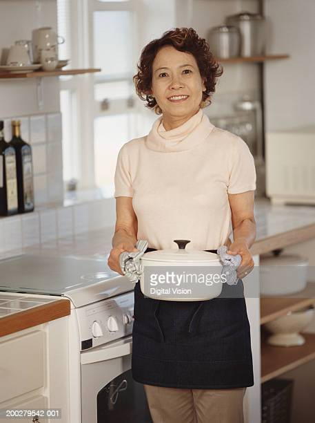 Senior woman in kitchen holding casserole dish, smiling, portrait