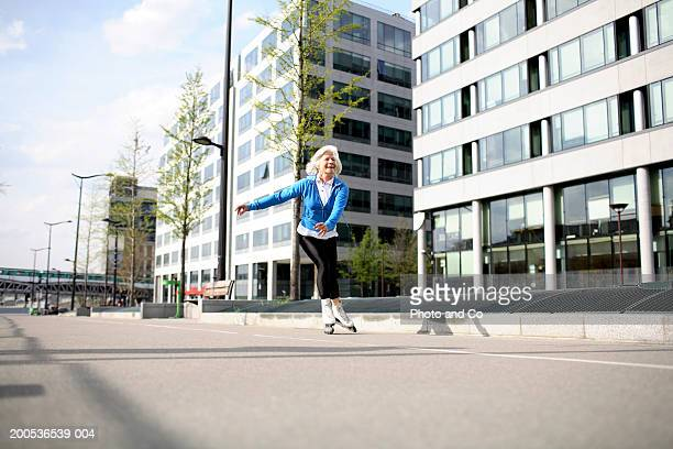 Senior woman in line skating on pavement