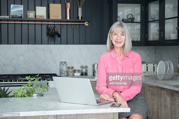 Senior woman in modern kitchen with laptop, smiling
