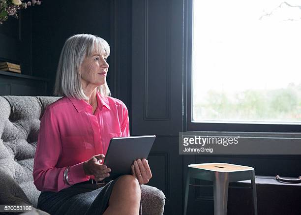 Donna anziana in Camicetta rosa con talea digitale