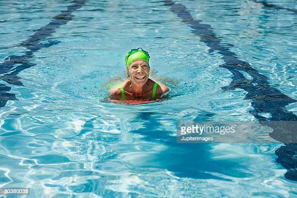 Senior woman in swimming pool using kickboard