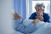 Senior woman holding hand of sick man lying in hospital bed