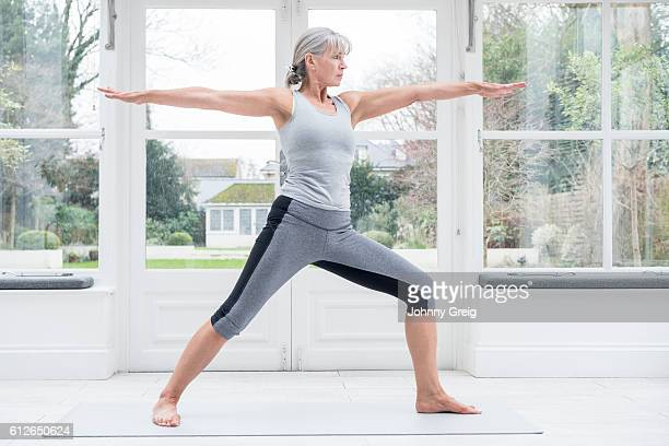 Senior woman in warrior yoga position with arms outstreteched