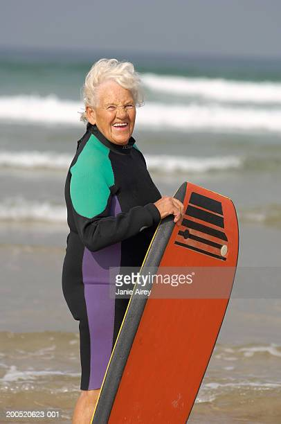 Senior woman, in wetsuit, holding boogie board at beach, portrait