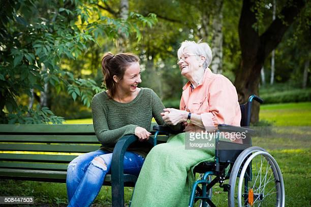 senior Frau im Rollstuhl mit jungen Frau lacht