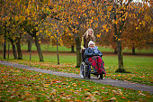 Senior woman in wheelchair accompanied by a carer