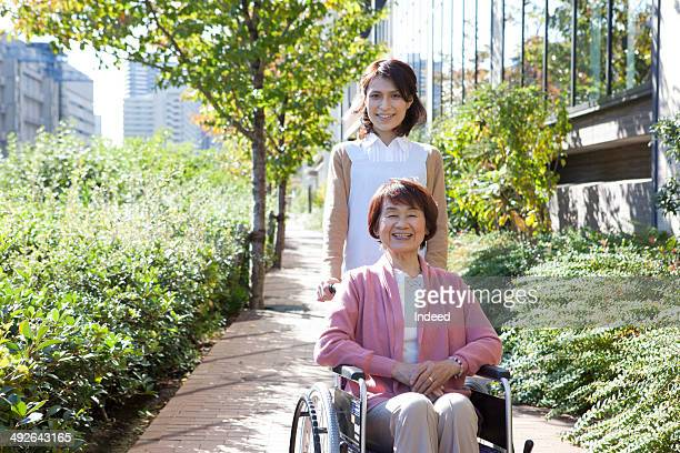 Senior woman in wheelchair and caregiver on street
