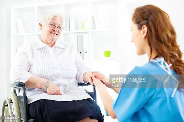 Senior femme en fauteuil roulant au bureau de médecins.