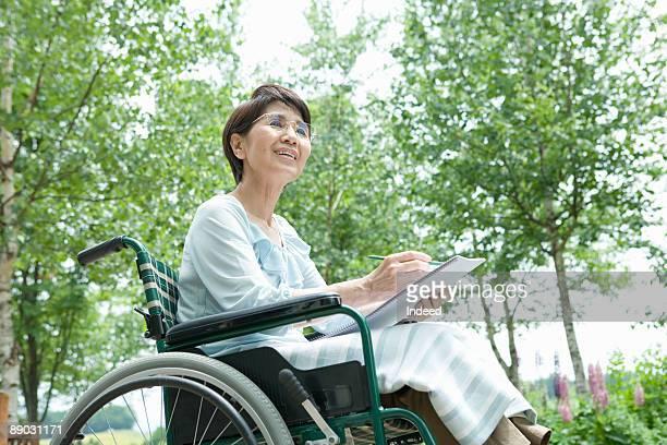 Senior woman in wheelchair drawing on sketchbook