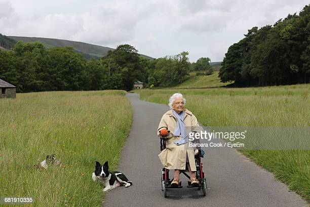 Senior Woman In Wheelchair On Empty Road