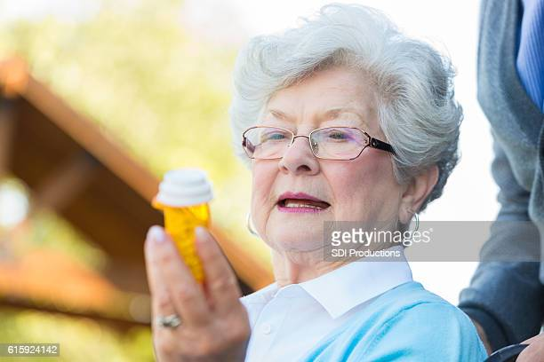 Senior woman in wheelchair reads prescription medication label