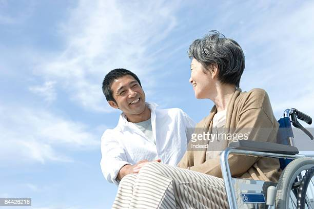 Senior woman in wheelchair smiling to man