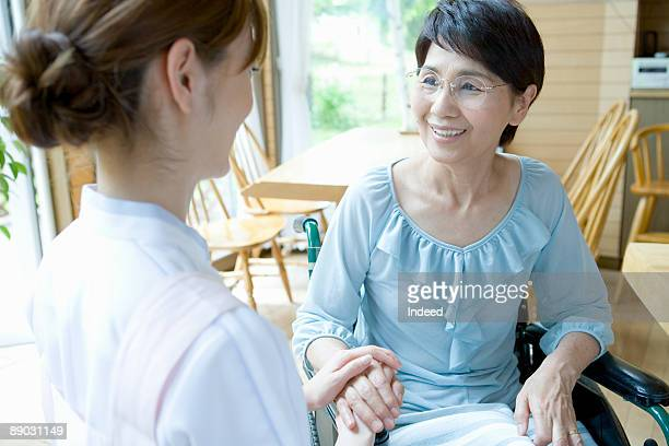 Senior woman in wheelchair smiling to nurse