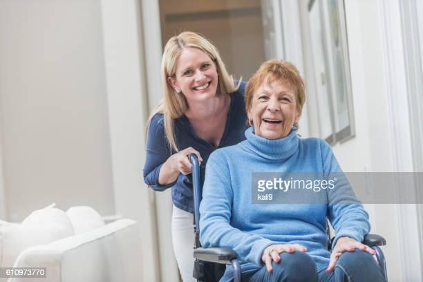 Senior donna in sedia a rotelle con badante a casa
