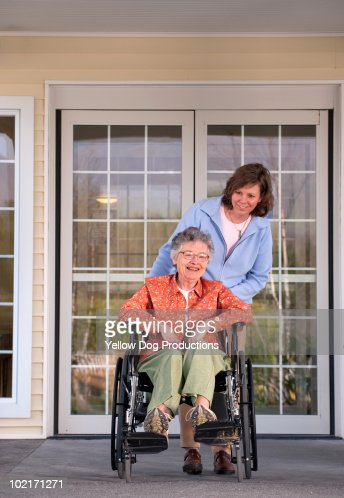 Senior woman in wheelchair with caregiver : Stock Photo