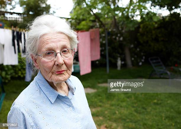 Senior woman in yard, clothesline in background