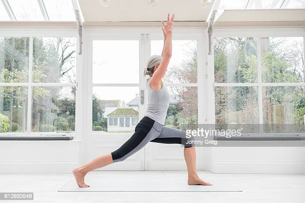 Senior woman in yoga post with arms raised