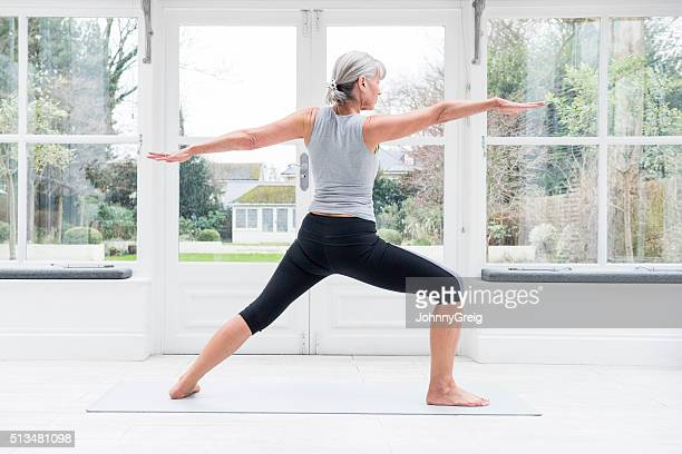 Senior woman in yoga warrior pose with arms outstretched