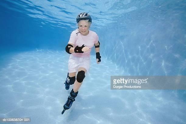 Senior woman inline skating underwater in pool