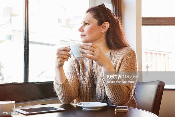 senior woman is drinking coffee in cafe