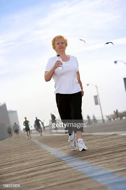 A senior woman is power walking on the boardwalk.