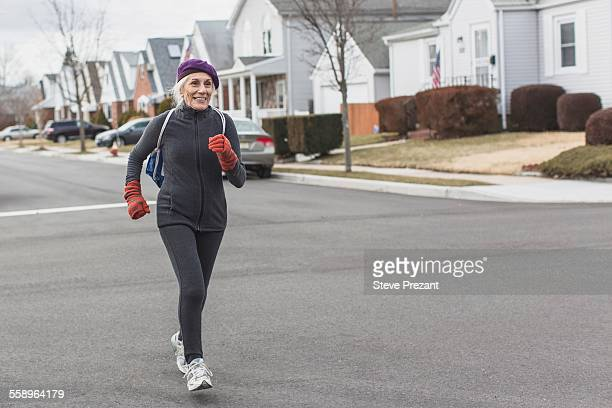 Senior woman jogging in street